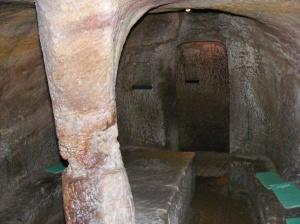 """Üks koobastiku peamistest ruumidest, ääres pingid ja keskel laud, millel on lisaks """"kausile"""" erinevaid kritseldusi kraabitud"""
